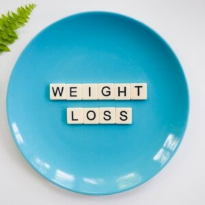 Image of a blue plate with the words weight loss spelled out on it
